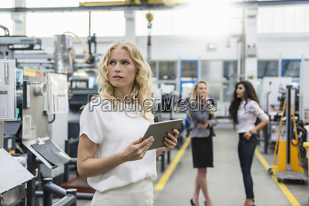 woman holding tablet in factory shop