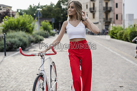 smiling teenage girl pushing bicycle in