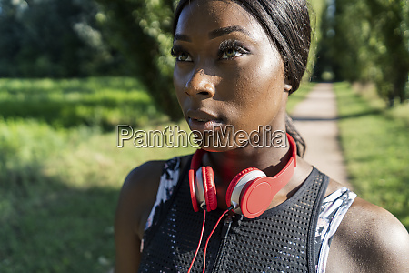 young athlete in nature listening music
