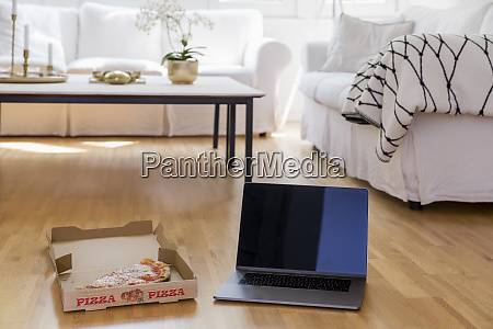 pizza box with pizza and laptop