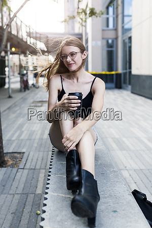 young woman sitting on a wall
