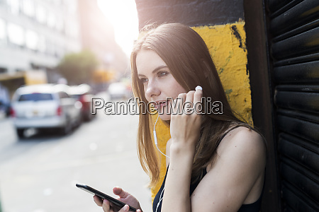 young woman leaning on street corner