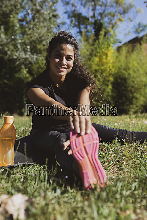sporty young woman stretching her leg