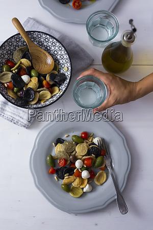 woman serving mediterranean orecchiette with tomato