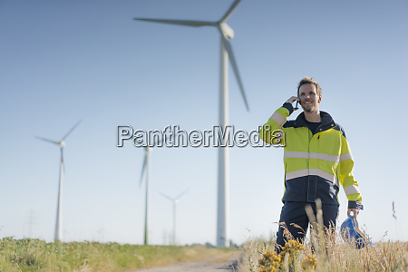 smiling engineer standing in a field