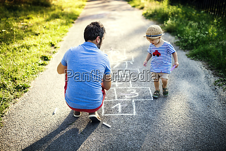 father playing hopscotch together with his