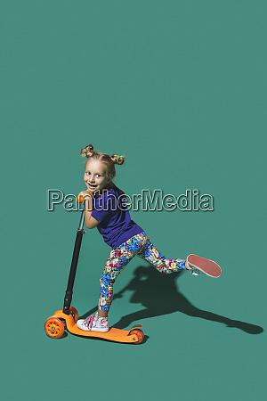 playful girl riding scoter on green