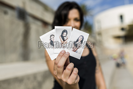 womans hand holding instant photos of