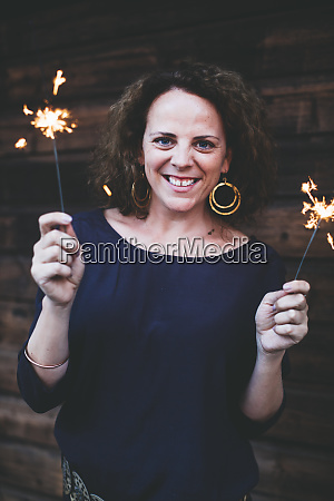 smiling woman holding sparklers