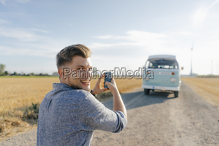 smiling young man taking cell phone