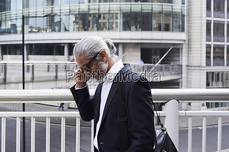 grey haired senior businessman talking on