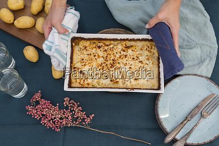 woman serving potato mincemeat gratin partial