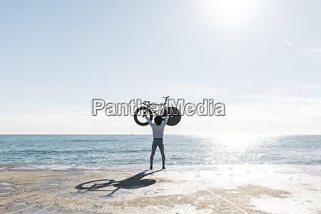 man lifting his bike on the