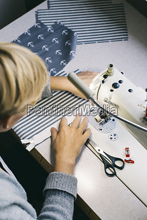 woman using sewing machine on table