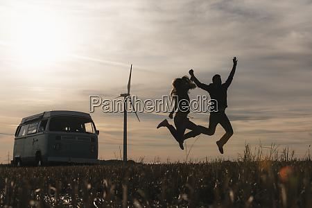exuberant couple jumping at camper van