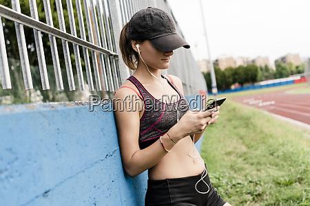 teenage girl using smartphone and earphone