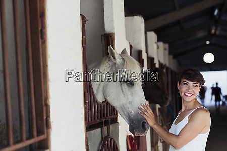 portrait of happy woman stroking horse