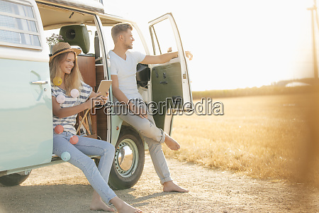 young couple relaxing at camper van