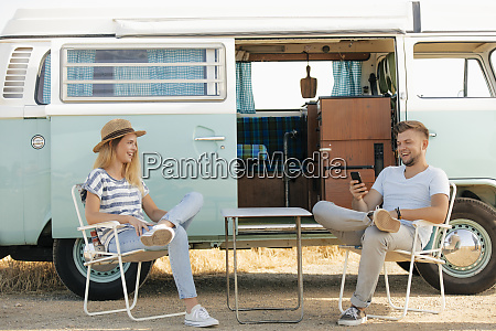 happy young couple sitting on camping