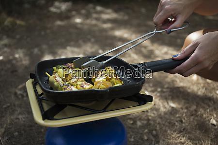 woman frying vegetable skewer on gas