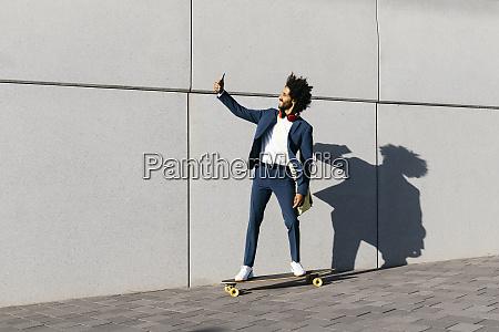 young businessman riding skateboard along a