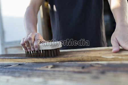 craftswoman using brush on piece of