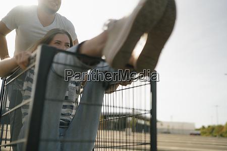 carefree young man pushing girlfriend in