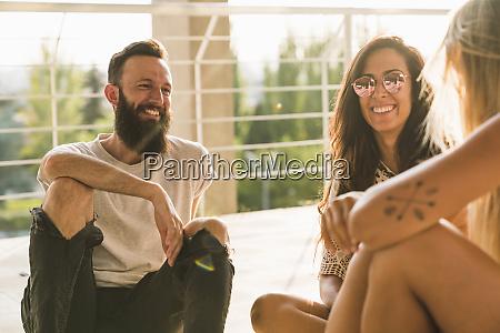 happy friends sitting down relaxing in