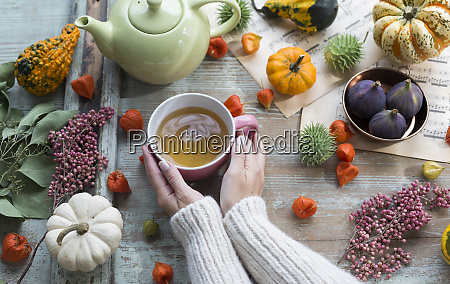 woman warming her hands on cup