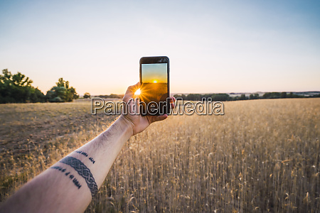 man taking photo of sunset and