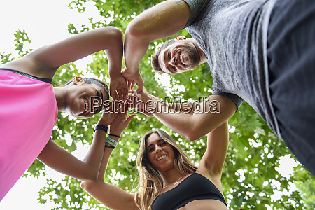 young sports team stacking hands celebrating
