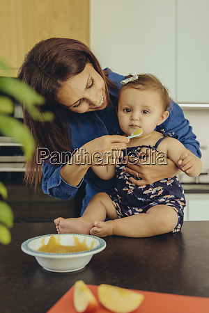 mother helping baby daughter eating fruit