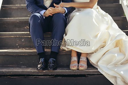 bridal couple sitting on stairs outdoors