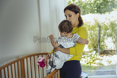 mother putting her baby girl to