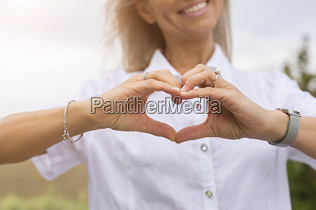 mature woman shaping heart with her