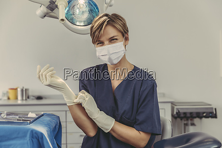 dental surgeon wearing surgical mask putting
