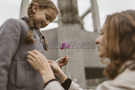 little girl watching mothers hands buttoning