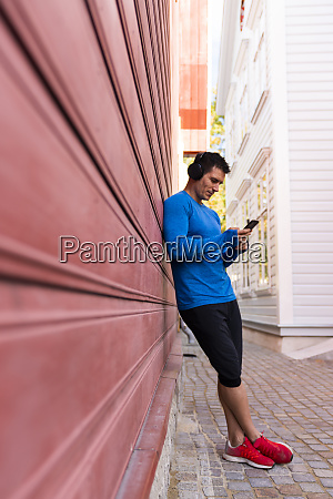 athlete leaning against house wall with