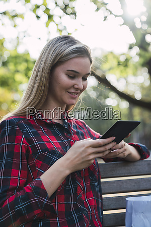 smiling young woman sitting on bench