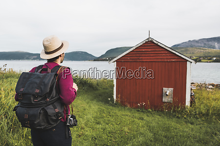 young man with backpack exploring red