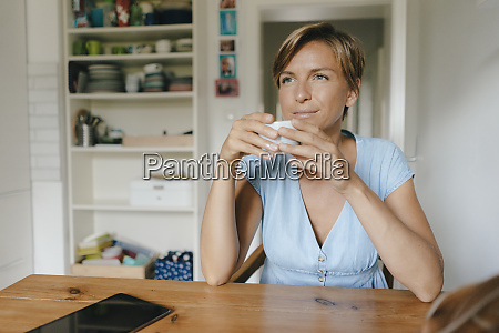 woman sitting at table at home