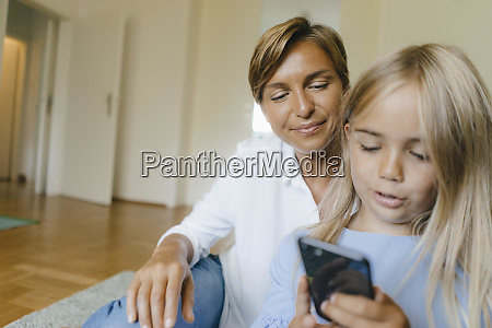 mother and daughter looking at smartphone