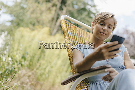 woman sitting in garden on chair