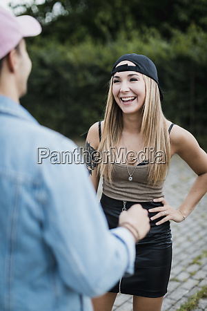 young woman laughing at man outdoors