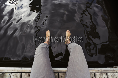 man sitting on jetty at a