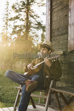 young man sitting on veranda of
