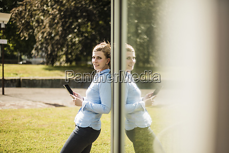 smiling woman leaning against glass front