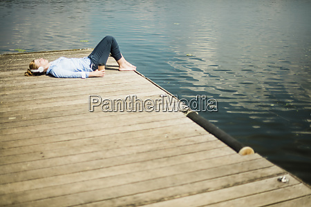 woman lying on jetty at a