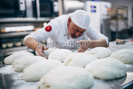 baker working with dough in bakery