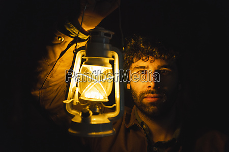 portrait of man holding storm lantern